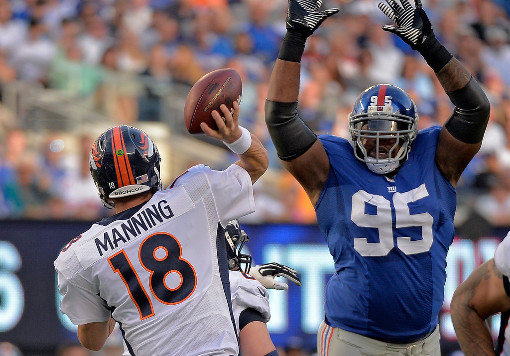Description of . New York Giants' Shaun Rodgers (95) attempts to block a pass by Denver Broncos quarterback Peyton Manning (18) during the second quarter September 15, 2013 MetLife Stadium. (Photo by John Leyba/The Denver Post)