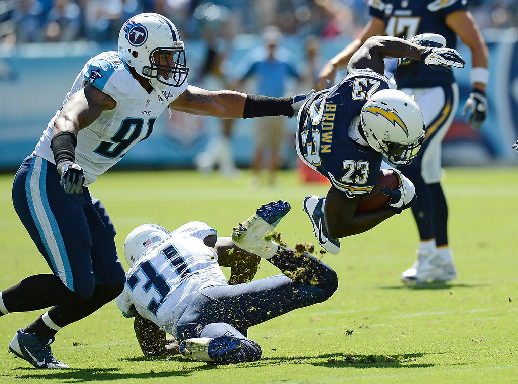 Description of . San Diego Chargers running back Ronnie Brown (23) is brought down by Tennessee Titans defenders Bernard Pollard (31) and Derrick Morgan (91) in the second quarter of an NFL football game on Sunday, Sept. 22, 2013, in Nashville, Tenn. (AP Photo/Mark Zaleski)