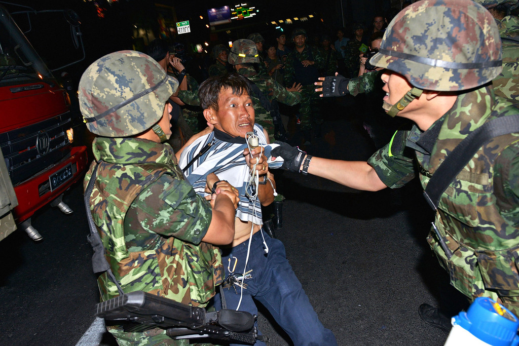 Description of . A protester is dragged away by Thai army soldiers while taking part in anti-coup rally on May 23, 2014 in Bangkok, Thailand. Anti-coup protesters rallied in Bangkok's shopping district, a day after the military seized control in a bloodless coup. Minor scuffles broke out during the rally and at least four protesters were detained by the army. Martial law imposes a 10pm to 5am curfew and bans public assembly. (Photo by Rufus Cox/Getty Images)