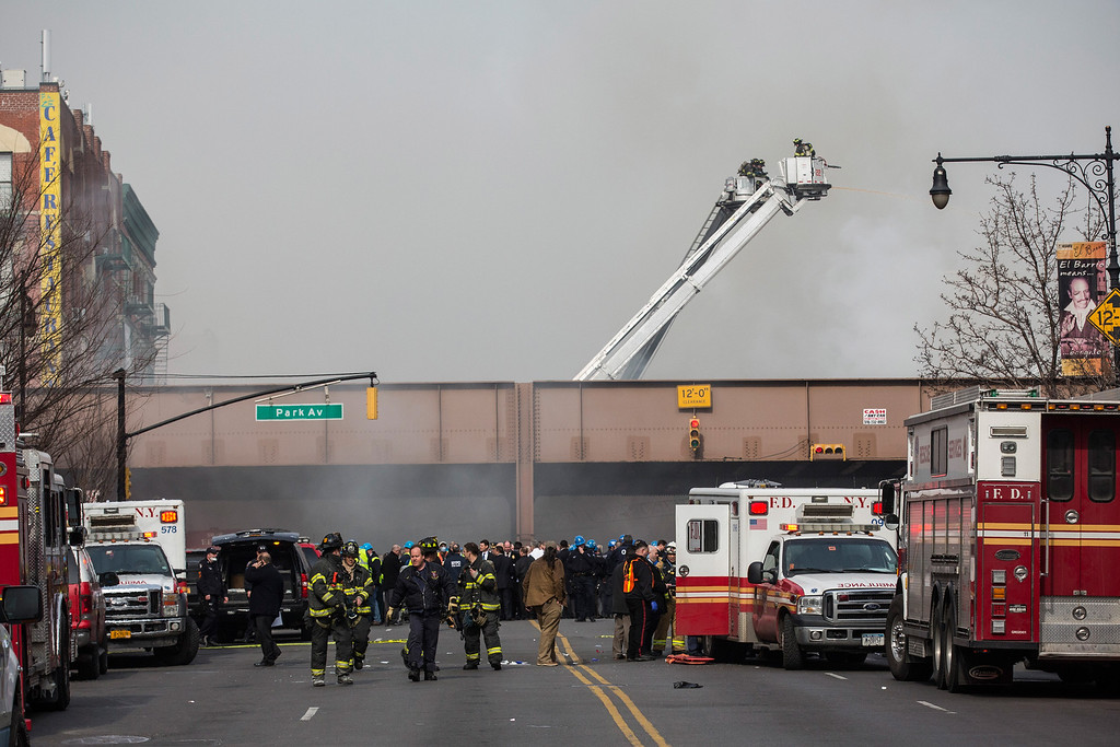 Description of . Firefighters from the Fire Department of New York (FDNY) respond to a 5-alarm fire and building collapse at 1646 Park Ave in the Harlem neighborhood of Manhattan March 12, 2014 in New York City.  (Photo by Andrew Burton/Getty Images)
