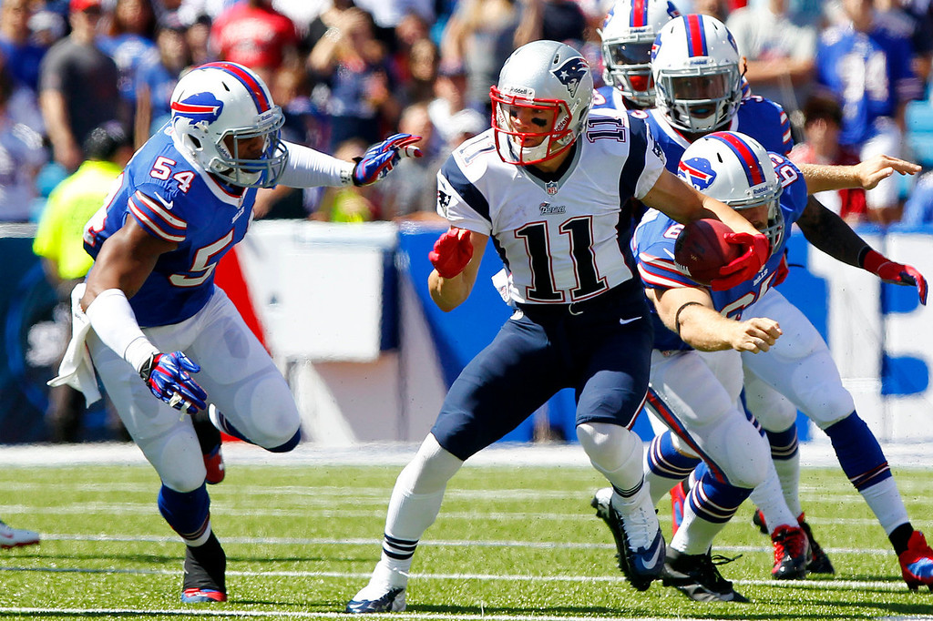 Description of . New England Patriots' Julian Edelman (11) returns a punt as Buffalo Bills' Marcus Dowtin (54) attempts to tackle him during the first half of an NFL football game on Sunday, Sept. 8, 2013, in Orchard Park. (AP Photo/Bill Wippert)