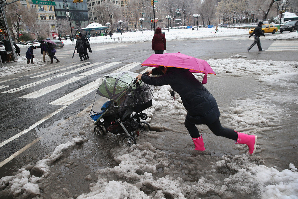 Description of . A nanny pushes a child through the slushy intersection of Broadway and 14th Street at Union Square on February 5, 2014 in New York City. New Yorkers, like millions of Americans in the northeast, dealt with the latest winter storm, which dumped 4 inches of snow on Central Park before turning to rain.  (Photo by John Moore/Getty Images)