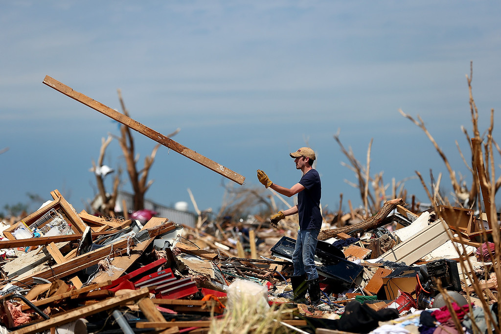 Description of . MOORE, OK - MAY 23:  Kyle Gray digs through the remains of his grandmother's destroyed home on May 23, 2013 in Moore, Oklahoma. The two-mile-wide Category 5 tornado touched down May 20 killing at least 24 people and leaving behind extensive damage to homes and businesses. U.S. President Barack Obama promised federal aid to supplement state and local recovery efforts.  (Photo by Tom Pennington/Getty Images)