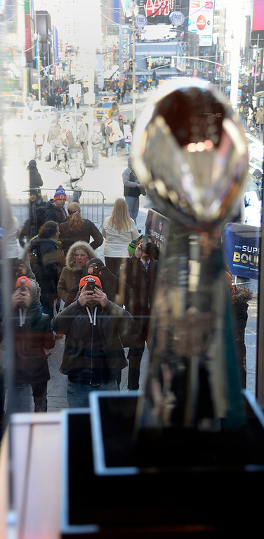 Description of . Super Bowl XLVlll fans take photos of the Vince Lombardi Trophy which was on display in Times Square. Fans flocked the streets to enjoy Super Bowl Boulevard where the NFL transformed a portion of Broadway into the sports and entertainment hub of Super Bowl Week, January 29, 2014. (Photo by John Leyba/The Denver Post)