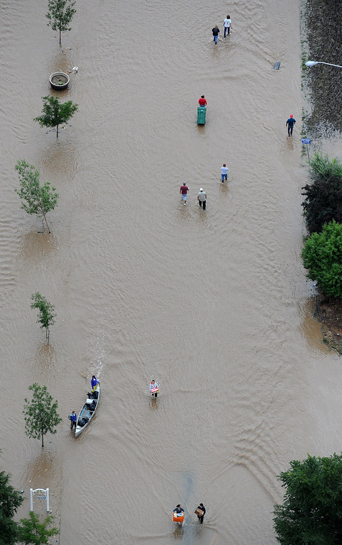 Description of . People walk down 37th street in Evans Colorado, carrying belongings recovered from flooded  homes in the area. Aerial photographs of the Platte River flooding cities and farms in Weld County Colorado. (Photo By Tim Rasmussen/The Denver Post)