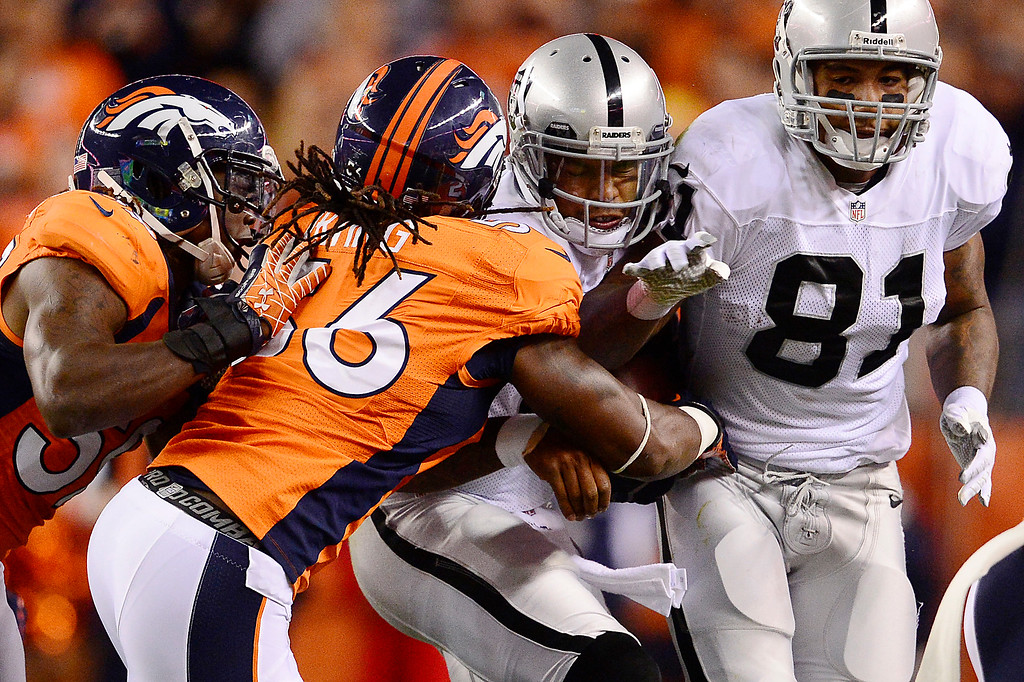 . Oakland Raiders quarterback Terrelle Pryor (2) is tackled by Denver Broncos linebacker Nate Irving (56) in the second quarter. The Denver Broncos took on the Oakland Raiders at Sports Authority Field at Mile High in Denver on September 23, 2013. (Photo by AAron Ontiveroz/The Denver Post)
