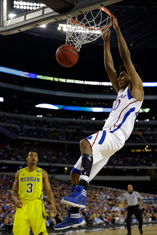 Description of . Kansas \' Kevin Young (40) dunks the ball against Michigan during the first half of a regional semifinal game in the NCAA college basketball tournament, Friday, March 29, 2013, in Arlington, Texas. (AP Photo/David J. Phillip)