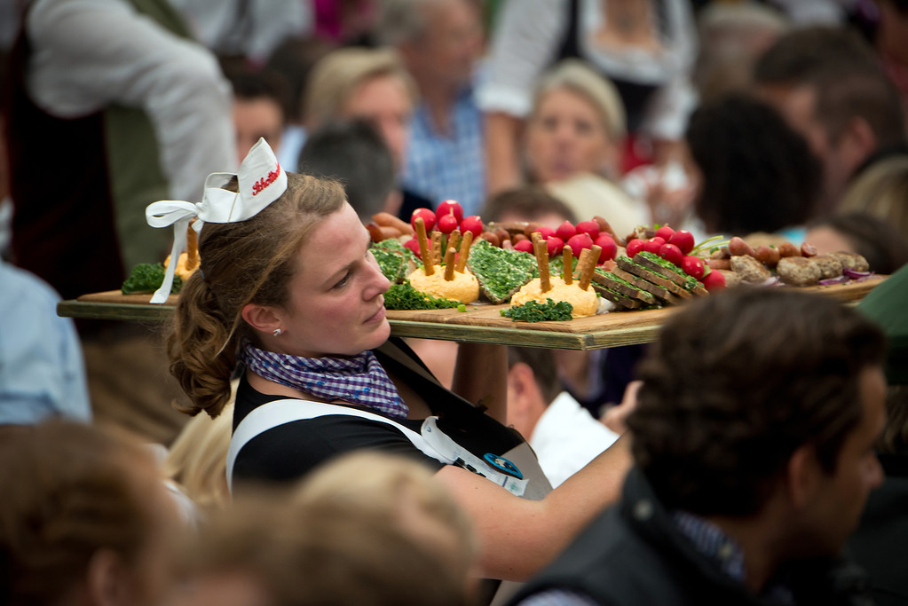 Description of . A waitress carries Bavarian food at the Oktoberfest 2013 beer festival at the Schottenhamel-tent at Theresienwiese on September 21, 2013 in Munich, Germany. Shortly before, Munich mayor Christian Ude (SPD) had tapped the first barrel with the traditional