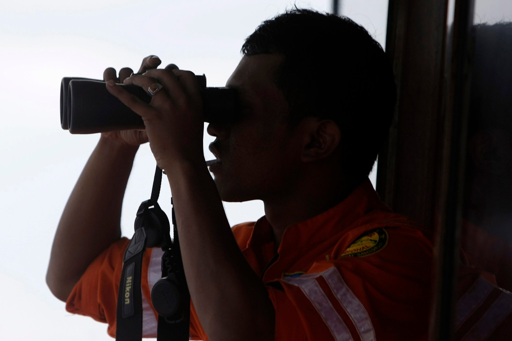 Description of . An Indonesian Search And Rescue (SAR) member looks through binoculars during a search operation for the missing Malaysian Airlines airplane in the Malacca straits, near Aceh Sea, Sumatera, Indonesia, 12 March 2014.  EPA/HOTLI SIMANJUNTAK