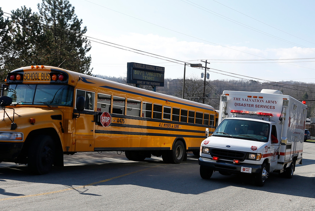 Description of . A Salvation Army disaster services vehicle drives past a school bus onto the campus of the Franklin Regional School District where several people were stabbed at Franklin Regional High School, Wednesday, April 9, 2014 in Murrysville, Pa., near Pittsburgh. The suspect, a male student, was taken into custody and being questioned. (AP Photo/Keith Srakocic)