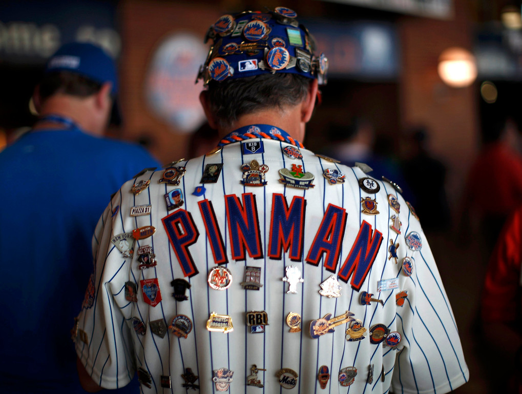 Description of . A New York Mets fan covered in baseball pins arrives for Major League Baseball's All-Star Game in New York, July 16 2013. REUTERS/Mike Segar