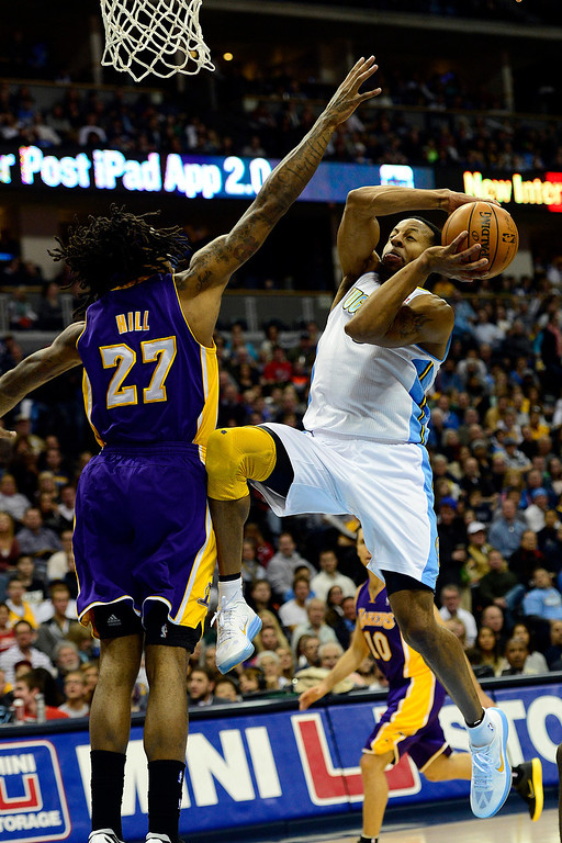 Description of . Denver Nuggets shooting guard Andre Iguodala (9) drives on Los Angeles Lakers center Jordan Hill (27) during the first half at the Pepsi Center on Wednesday, December 26, 2012. AAron Ontiveroz, The Denver Post
