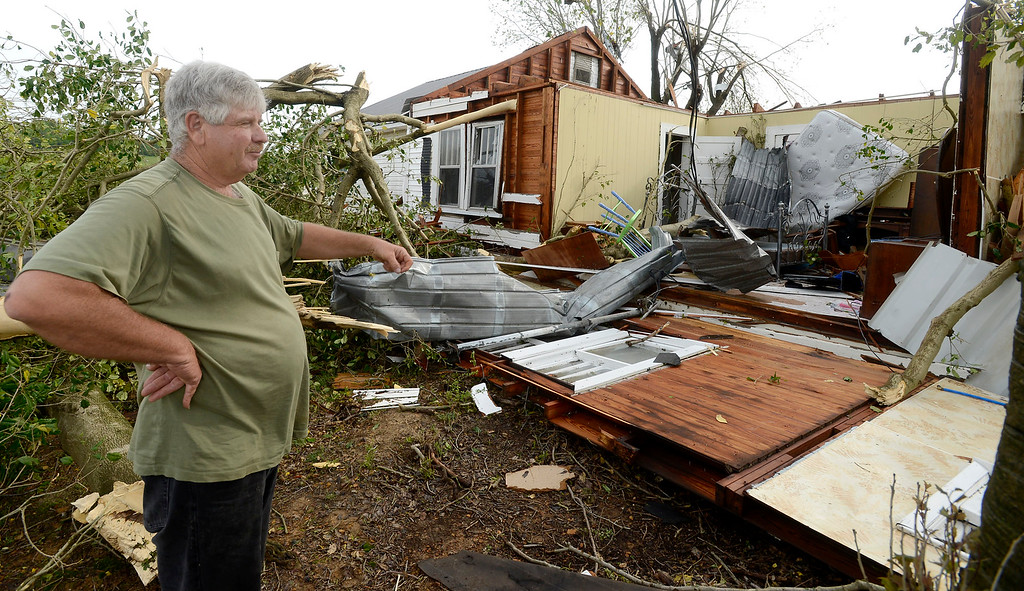Description of . Dennis Nix stands outside his father's destroyed house in the Straight Mountain community of Blount County, Ala., Tuesday, April 29, 2014.  Nix and his father were inside when a possible tornado struck but they were not injured.   (AP Photo/ AL.com, Mark Almond)