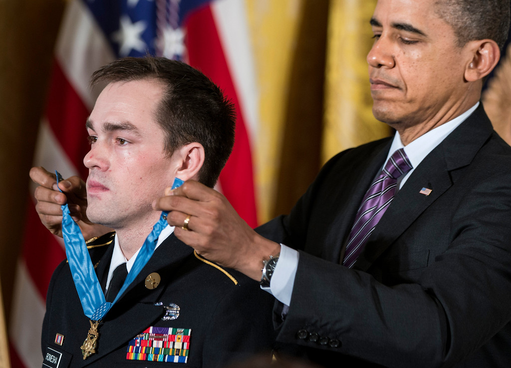 Description of . US President Barack Obama awards former US Army Staff Sargent Clinton Romesha the Medal of Honor during a ceremony in the East Room of the White House February 11, 2013 in Washington, DC.  AFP PHOTO/Brendan SMIALOWSKI/AFP/Getty Images