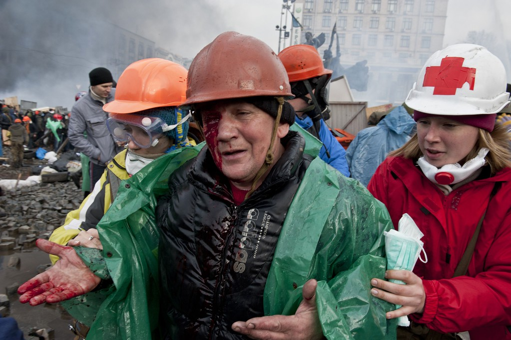 Description of . A wounded anti-government protester is evacuated during clashes with riot police on Kiev's Independence square on February 19, 2014.  AFP PHOTO / PIERO  QUARANTA/AFP/Getty Images