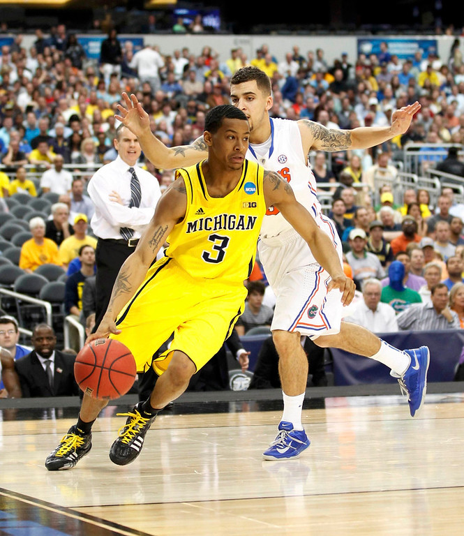 . Michigan Wolverines guard Trey Burke (L) goes to the basket against Florida Gators guard Scottie Wilbekin in their South Regional NCAA men?s basketball game in Arlington, Texas March 31, 2013. REUTERS/Mike Stone