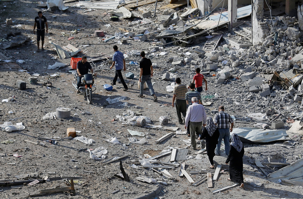 Description of . Palestinians walk by the rubble of destroyed houses in the heavily bombed town of Beit Hanoun, Gaza Strip, close to the Israeli border, Friday, Aug. 1, 2014. A three-day Gaza cease-fire that began Friday quickly unraveled, with Israel and Hamas accusing each other of violating the truce. (AP Photo/Lefteris Pitarakis)