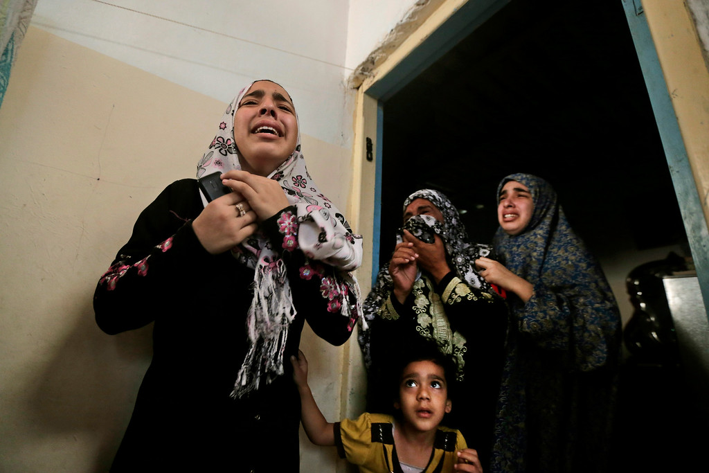 Description of . Palestinian mourners cry as the bodies of brothers Abdullah Al Amoudi, 18, and Bilal, 26, who were killed by an Israeli strike earlier near the Abu Hussein school, are brought into their home during their funeral at Jebaliya refugee camp, northern Gaza Strip,  Wednesday, July 30, 2014. According to the family, the brothers were killed outside the family home, across the street from the U.N. school. Several Israeli tank shells slammed into the crowded U.N. school used as shelter for refugees in the Gaza war early on Wednesday, killing over a dozen people, a Palestinian health official and a U.N. official said. (AP Photo/Lefteris Pitarakis)