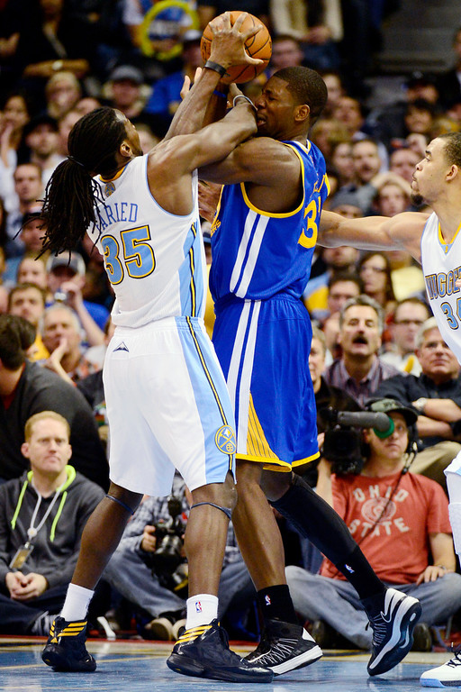 Description of . Denver Nuggets small forward Kenneth Faried (35) defends Golden State Warriors center Festus Ezeli (31) during the second half of the Nuggets' 116-105 win at the Pepsi Center on Sunday, January 13, 2013. AAron Ontiveroz, The Denver Post