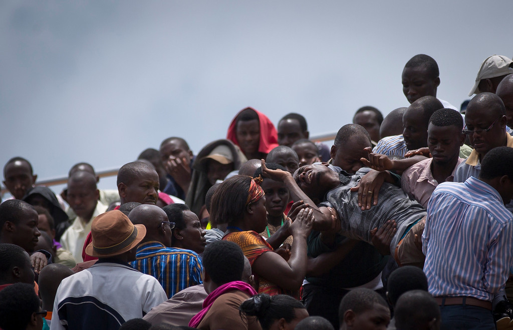 Description of . A wailing and distraught Rwandan man, one of dozens overcome by grief at recalling the horror of the genocide, is carried away to receive help during a public ceremony to mark the 20th anniversary of the Rwandan genocide, at Amahoro stadium in Kigali, Rwanda Monday, April 7, 2014.  (AP Photo/Ben Curtis)