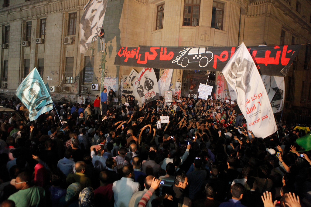 Description of . Members of Egypt's April 6 Youth Movement shout anti-Muslim Brotherhood slogans and wave flags depicting their members killed in the revolution during a rally in front of general prosecutor's office in Cairo, Egypt, Saturday, April 6, 2013. Arabic reads,