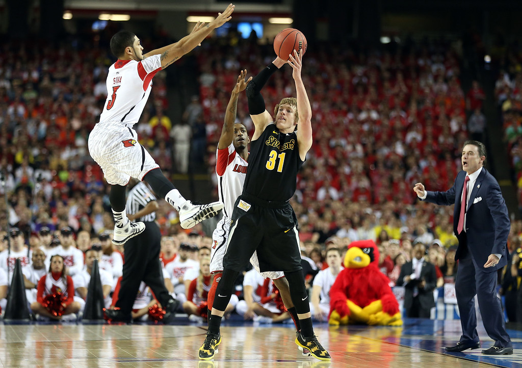 Description of . ATLANTA, GA - APRIL 06:  Ron Baker #31 of the Wichita State Shockers looks to pass as he is pressured by Peyton Siva #3 and Russ Smith #2 of the Louisville Cardinals during the 2013 NCAA Men's Final Four Semifinal at the Georgia Dome on April 6, 2013 in Atlanta, Georgia.  (Photo by Andy Lyons/Getty Images)