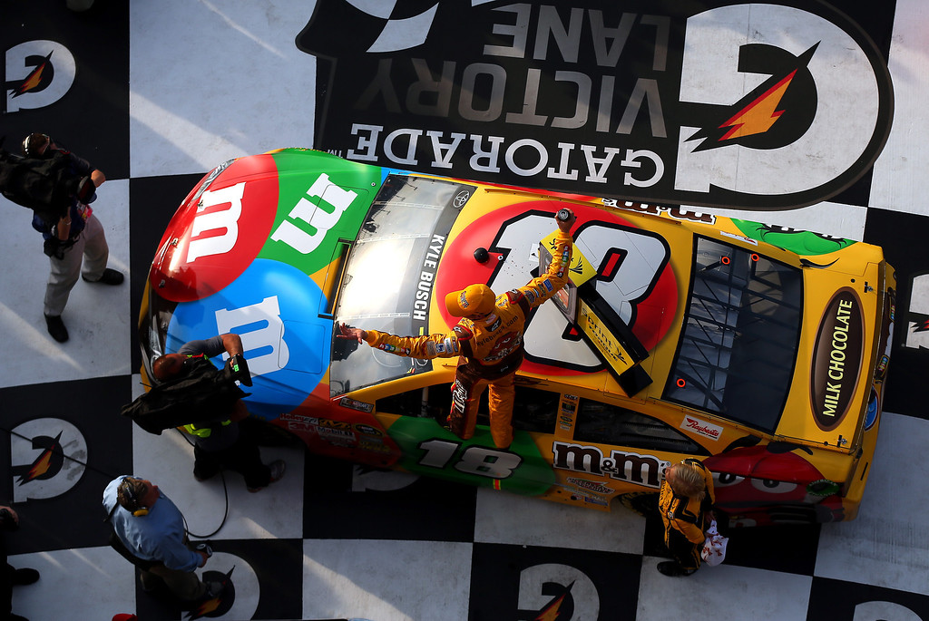 Description of . Kyle Busch, driver of the #18 M&M\'s Toyota, celebrates in Victory Lane after winning the NASCAR Sprint Cup Series Budweiser Duel 2 at Daytona International Speedway on February 21, 2013 in Daytona Beach, Florida.  (Photo by Mike Ehrmann/Getty Images)