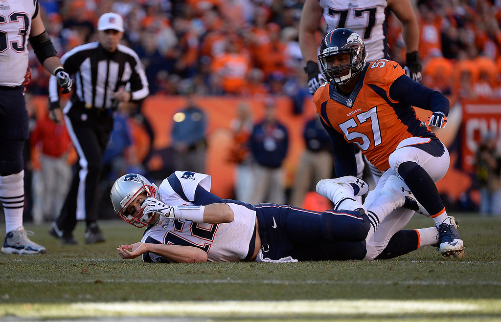 Description of . New England Patriots quarterback Tom Brady (12) is sacked by Denver Broncos defensive end Jeremy Mincey (57) in the fourth quarter. The Denver Broncos take on the New England Patriots in the AFC Championship game at Sports Authority Field at Mile High in Denver on January 19, 2014. (Photo by AAron Ontiveroz/The Denver Post)