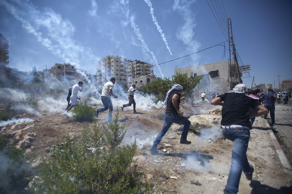 Description of . Palestinians run for cover during clashes with Israeli soldiers following a protest against the war in the Gaza Strip, outside Ofer, an Israeli military prison near the West Bank city of Ramallah, Friday, Aug. 1, 2014. (AP Photo/Majdi Mohammed)