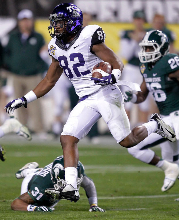 Description of . TCU wide receiver Josh Boyce (82) picks up a first down against Michigan State during the first half of the Buffalo Wild Wings Bowl NCAA college football game, Saturday, Dec. 29, 2012, in Tempe, Ariz. (AP Photo/Matt York)