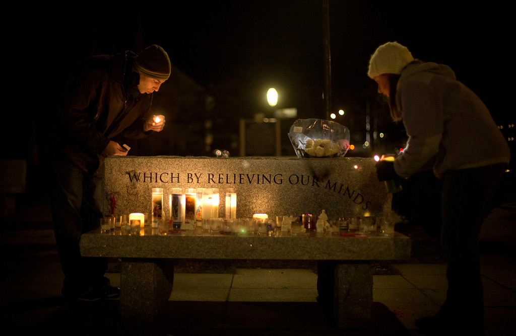Description of . Brian Tenenhaus, left, blows out a match after lighting a candle at a vigil outside the Edmond Town Hall with Lauren Foster, right, Saturday, Dec. 15, 2012, in Newtown, Conn. A gunman walked into Sandy Hook Elementary School in Newtown Friday and opened fire, killing 26 people, including 20 children. (AP Photo/David Goldman)