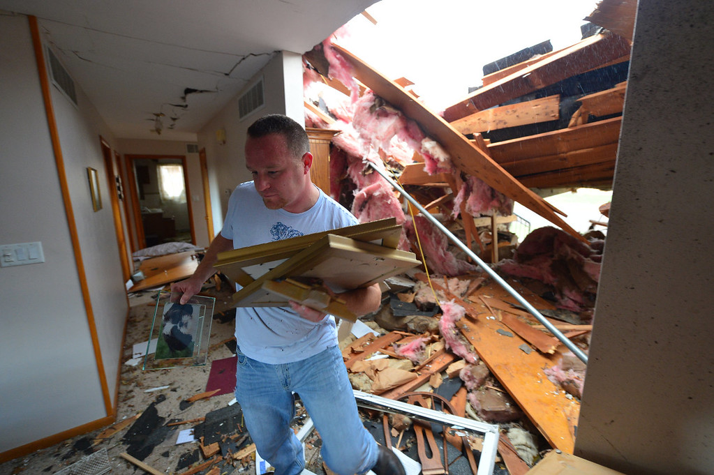 Description of . Josh Ramsey recovers items from a house of a family friend after a tornado left a path of devastation through the north end of Pekin, Ill., hitting right about noon Sunday, Nov. 17, 2013. Intense thunderstorms and tornadoes swept across the Midwest on Sunday, causing extensive damage in several central Illinois communities while sending people to their basements for shelter. (AP Photo/Journal Star, Fred Zwicky)