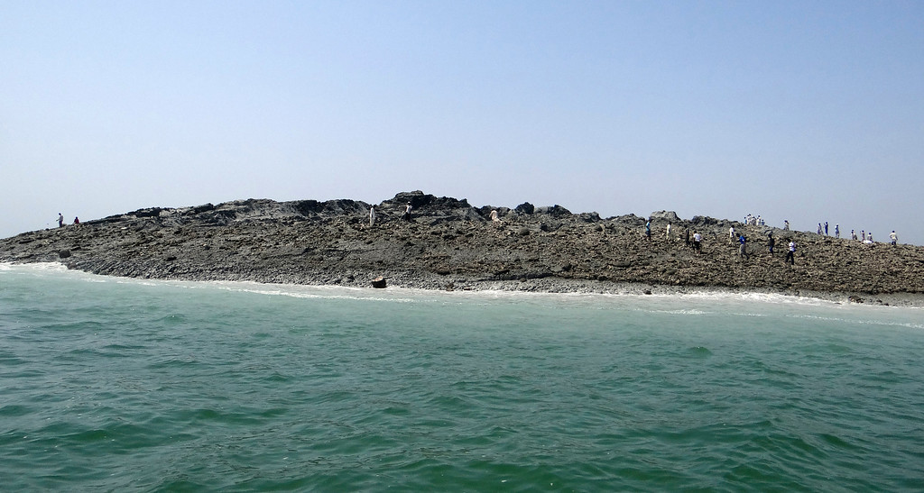 Description of . In this photo released by the Gwadar local government office on Wednesday, Sept 25, 2013, people walk on an island that reportedly emerged off the Gwadar coastline in the Arabian Sea. A deadly magnitude 7.7 earthquake struck in the remote district of Awaran in Pakistan's Baluchistan province with enough force to create a small island visible off the southern coast, Pakistani officials said. (AP Photo/Gwadar local government office)