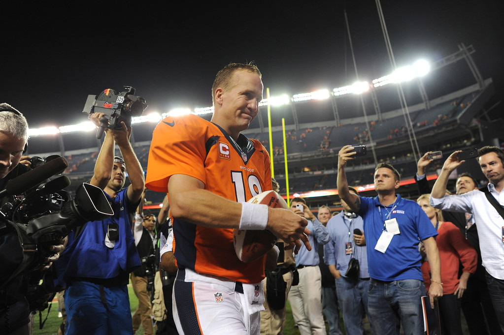 Description of . Denver Broncos quarterback Peyton Manning (18) walks away with the Player of the game ball after the Broncos defeated the Ravens 49-24. Denver Broncos Baltimore Ravens September 5, 2013 at Sports Authority at Mile High. (Photo by Joe Amon/The Denver Post)