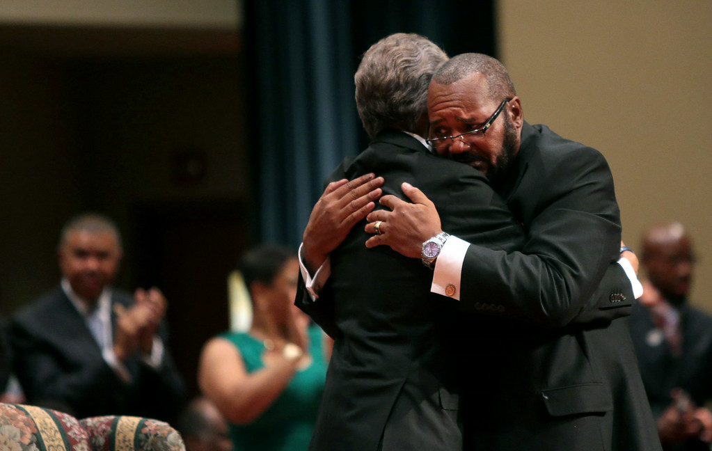 Description of . Pastor Charles Ewing, the uncle of Michael Brown, embraces Rev. Al Sharpton (L) after delivering a eulogy during the funeral of Michael Brown inside Friendly Temple Missionary Baptist Church on August 25, 2014 in St. Louis Missouri. Michael Brown, an 18 year-old unarmed teenager, was shot and killed by Ferguson Police Officer Darren Wilson in the nearby town of Ferguson, Missouri on August 9. His death caused several days of violent protests along with rioting and looting in Ferguson.  (Photo by Robert Cohen-Pool/Getty Images)