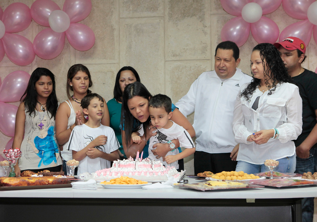 Description of . Venezuelan president Hugo Chavez (3rd R) celebrates the birthday of his daughter Maria Gabriela (C) with his family in La Habana March 13, 2012. Chavez said he will return home from Cuba where he is recovering from cancer surgery next Sunday, to head up a re-election campaign. REUTERS/Handout/Miraflores Palace