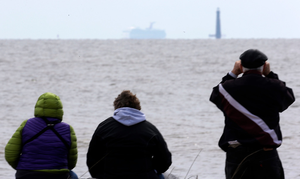 Description of . Residents sit on the shore and watch as the cruise ship Carnival Triumph is visible near Dauphin Island, Ala., Thursday, Feb. 14, 2013. The ship with over 1,000 passengers aboard has been idled for nearly a week in the Gulf of Mexico following an engine room fire. (AP Photo/Dave Martin)