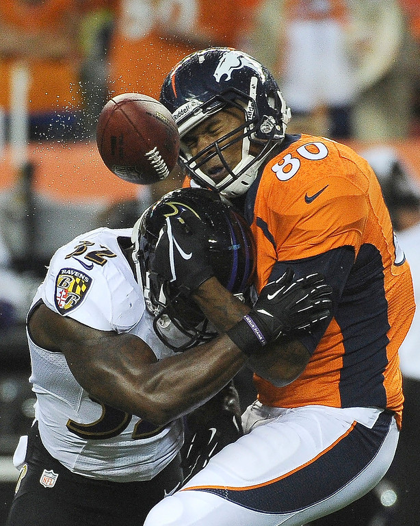 Description of . Denver Broncos tight end Julius Thomas (80) gets tackled by Baltimore Ravens strong safety James Ihedigbo (32) in the first quarter. The Denver Broncos took on the Baltimore Ravens in the first game of the 2013 season at Sports Authority Field at Mile High in Denver on September 5, 2013. (Photo by Tim Rasmussen/The Denver Post)
