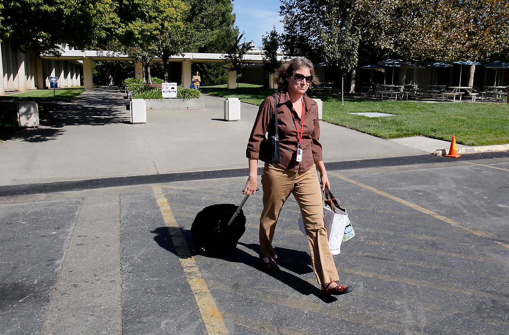 Description of . With her rolling backpack and bags in hand, Bronwyn Hogan, an employee of the U.S. Fish and Wildlife Service, leaves the federal offices in Sacramento, Calif., Tuesday, Oct. 1, 2013.  Hogan and other federal employees were forced to go on furlough due to the partial federal government  shutdown.(AP Photo/Rich Pedroncelli)