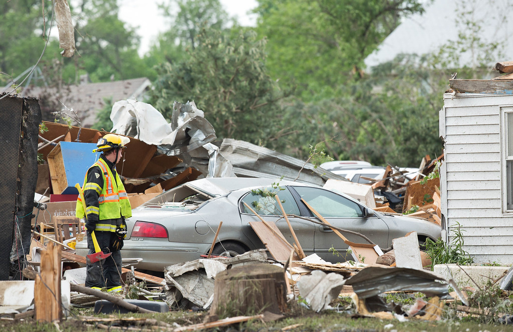 . A firefighter looks over the damaged cars and houses that were destroyed by a tornado that hit Pilger, Neb.,  on Monday, June 16, 2014.  The National Weather Service says the storm that struck northeast Nebraska appears to have produced four tornadoes, one of which ravaged the town of Pilger.   (AP Photo/The World-Herald, Ryan Soderlin)