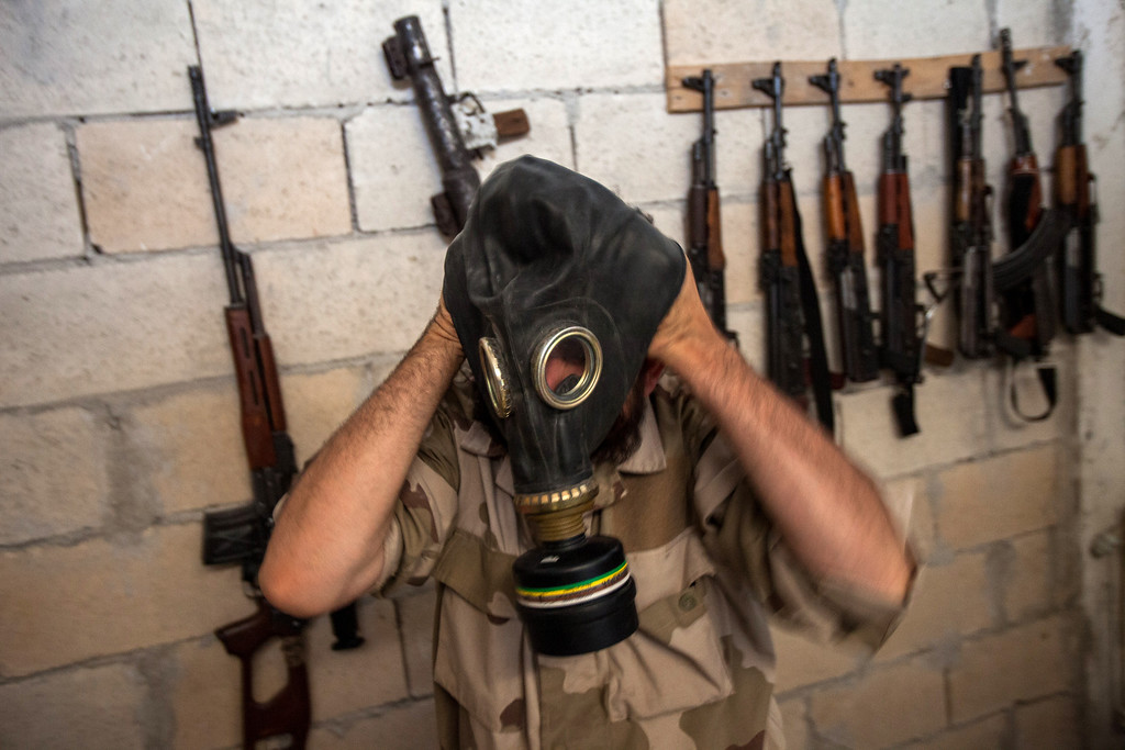 Description of . A Syrian rebel tries on a gas mask seized from a Syrian army factory in the northwestern province of Idlib on July 18, 2013. Western countries say they have handed over evidence to the UN that Bashar al-Assad's forces have used chemical arms in the two-year conflict. More than 100,000 people have died in the conflict, which morphed from a popular movement for change into an insurgency after the regime unleashed a brutal crackdown on dissent. DANIEL LEAL-OLIVAS/AFP/Getty Images