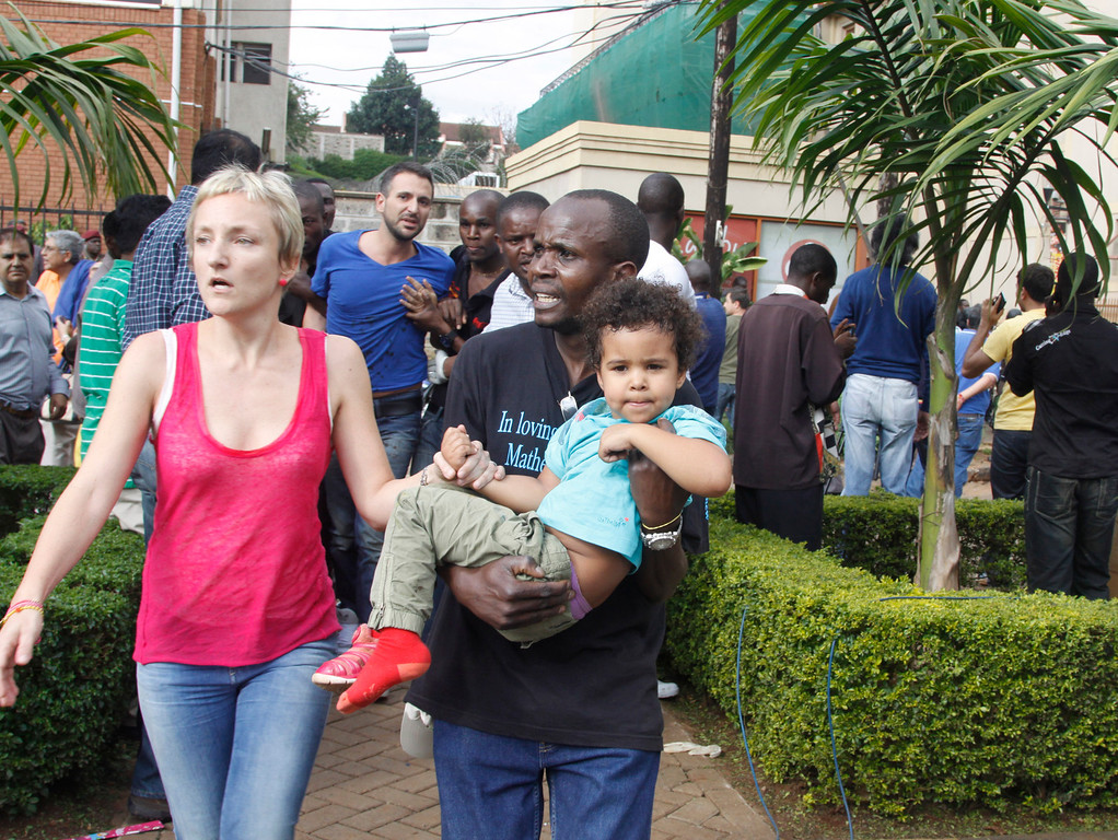 Description of . The mother and a security guard help a child outside the Westgate Mall in Nairobi, Kenya Saturday, Sept. 21 2013, after gunmen threw grenades and opened fire during an attack that left multiple dead and dozens wounded.  (AP Photo/Khalil Senosi)
