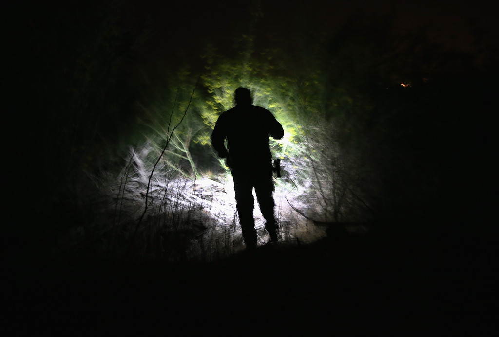 Description of . PENITAS TX - APRIL 11:  A U.S. Border Patrol agent searches in dense brush for undocumented immigrants who had crossed from Mexico into the United States on April 11, 2013 in Penitas, Texas. In the last month the Border Patrol\'s Rio Grande Valley sector has seen a spike in the number of immigrants crossing the river from Mexico into Texas. With more apprehensions, they have struggled to deal with overcrowding while undocumented immigrants are processed for deportation. According to the Border Patrol, undocumented immigrant crossings have increased more than 50 percent in Texas\' Rio Grande Valley sector in the last year. Border Patrol agents say they have also seen an additional surge in immigrant traffic since immigration reform negotiations began this year in Washington D.C. Proposed reforms could provide a path to citizenship for many of the estimated 11 million undocumented workers living in the United States.  (Photo by John Moore/Getty Images)