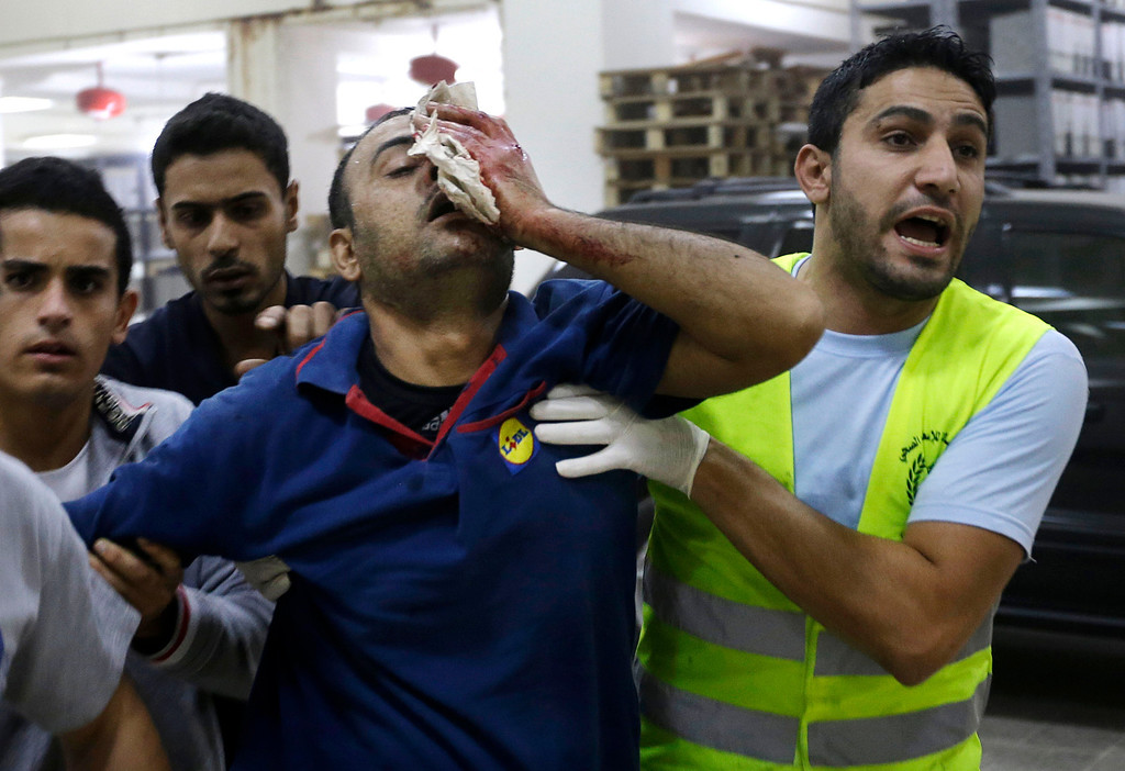 . Hezbollah civil defense workers, help an injured man, at the scene where two explosions have struck near the Iranian Embassy killing many, in Beirut, Lebanon, Tuesday, Nov. 19, 2013.  (AP Photo/Hussein Malla)