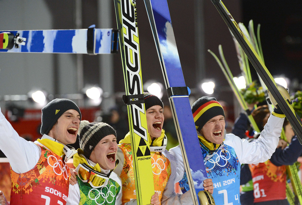 Description of . (from L) Germany's Andreas Wank, Germany's Marinus Kraus, Germany's Andreas Wellinger and Germany's Severin Freund  celebrate winning gold during the Men's Ski Jumping Team Flower Ceremony at the RusSki Gorki Jumping Center during the Sochi Winter Olympics on February 17, 2014, in Rosa Khutor, near Sochi.  KIRILL KUDRYAVTSEV/AFP/Getty Images