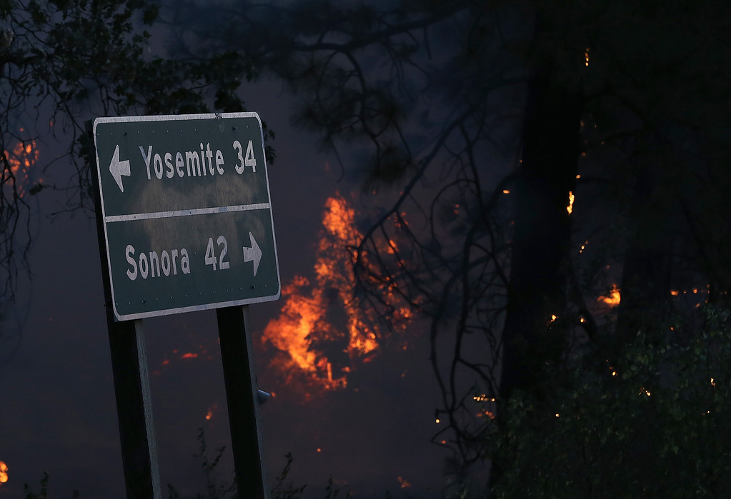 Description of . GROVELAND, CA - AUGUST 21:  Flames from the Rim Fire burn near a road sign pointing towards Yosemite on August 21, 2013 in Groveland, California. The Rim Fire continues to burn out of control and threatens 2,500 homes outside of Yosemite National Park. Over 400 firefighters are battling the blaze that is only 5 percent contained.  (Photo by Justin Sullivan/Getty Images)
