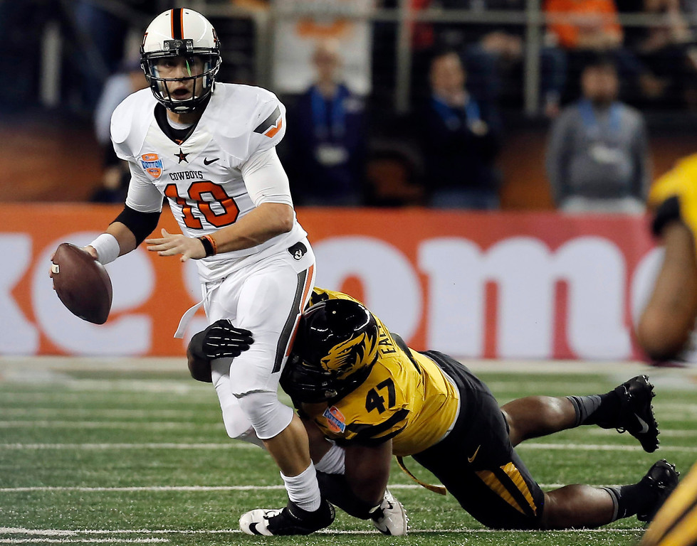 Description of . Missouri defensive lineman Kony Ealy (47) sacks Oklahoma State quarterback Clint Chelf (10) during the first half of the Cotton Bowl NCAA college football game on Friday, Jan. 3, 2014, in Arlington, Texas. (AP Photo/Brandon Wade)