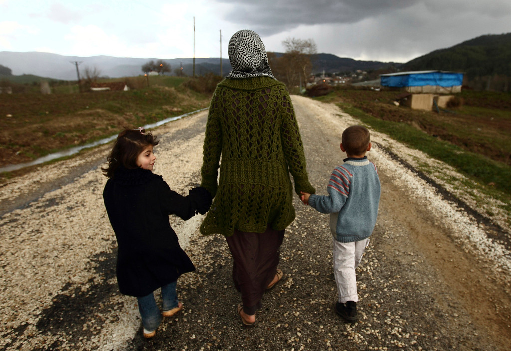 Description of . Sawssan  Abdelwahab, who fled Idlib in Syria, walks with her children outside the refugees camp near the Turkish-Syrian border in the southeastern city of Yayladagi February 16, 2012. REUTERS/Zohra Bensemra