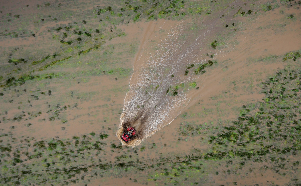 Description of . A unidentified man on ATV makes his way through pastureland outside Milliken. Aerial photographs of the South Platte River flooding cities and farms in Weld County Colorado. (Photo By Tim Rasmussen/The Denver Post)