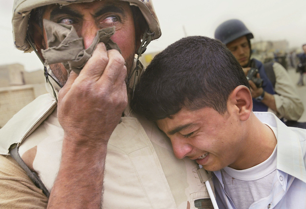 Description of . Khudair Al-Amiri (L) cries with his son, Ali Al-Amiri, as they are reunited after the father\'s return to his hometown as a translator for American Marines April 7, 2003 in Qal\'at Sukkar, Iraq. Al-Amiri fled Iraq after the first Gulf war and returned with the 24th Marine Expeditionary Unit, seeing members of his family and village for the first time in over a decade. (Photo by Chris Hondros/Getty Images)